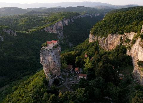 "The Katskhi Pillar, where an elderly Georgian monk has lived for the past 24 years in order to be ""closer to God."" The monk has his food winched up by volunteers from the monastery below - Credit: Amos Chapple/RFE/RL"
