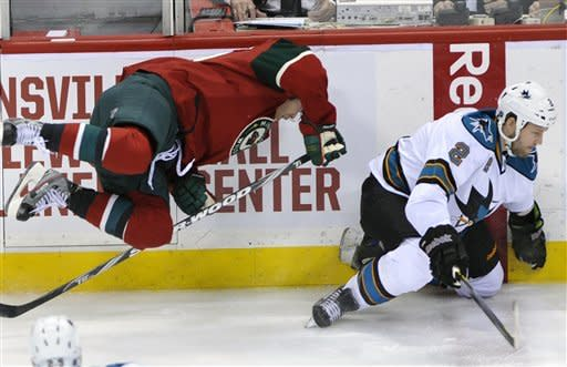 Minnesota Wild's Stephane Veilleux, left, is upended after a collision with San Jose Sharks' Joe Pavelski in the first period of an NHL hockey game on Sunday, Feb. 26, 2012, in St. Paul, Minn. (AP Photo/Jim Mone)