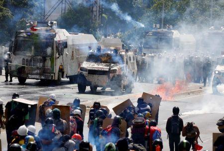 Opposition supporters clash with riot security forces while rallying against President Nicolas Maduro in Caracas