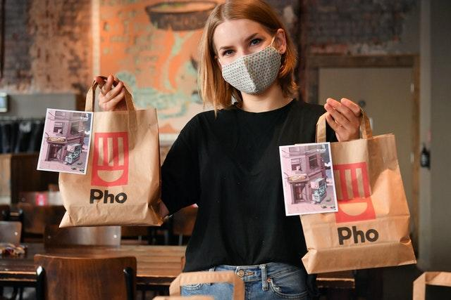 Staff member holds lunch bags at Pho