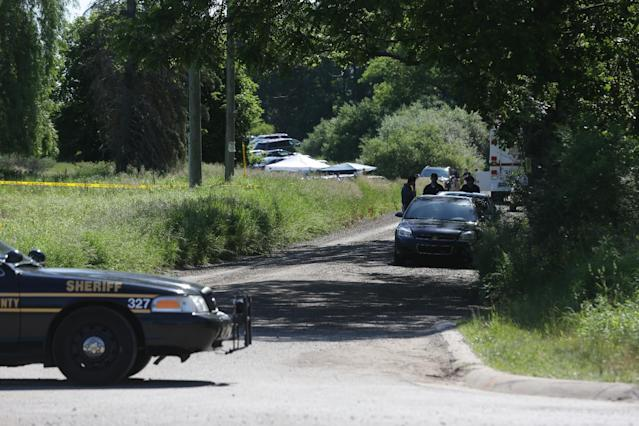 Law enforcement officials block the street to the scene in Oakland Township, Mich., Monday, June 17, 2013 where officials search for the remains of Teamsters union president Jimmy Hoffa who disappeared from a Detroit-area restaurant in 1975. (AP Photo/Carlos Osorio)