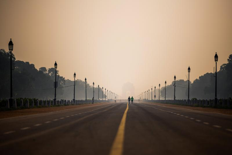 People walk along Rajpath street during a smoggy morning in New Delhi on October 15, 2020. (Photo by Jewel SAMAD / AFP) (Photo by JEWEL SAMAD/AFP via Getty Images)