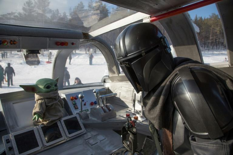 """A man wearing a costume of the StarWars protagonist Din Djarin poses onboard a giant replica of the Razor Crest, a gunship from the StarWars spinoff series """"The Mandalorian"""" in the city of Yakutsk"""