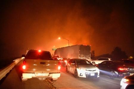 Freeway traffic comes to a standstill as a wind-driven wildfire burns in Sylmar, California