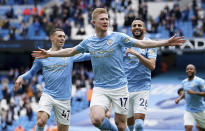 FILE - In this Sunday, May 23, 2021 file photo, Manchester City's Kevin De Bruyne, centre, Manchester City's Phil Foden, left, and Manchester City's Riyad Mahrez celebrate scoring their side's first goal during the English Premier League soccer match between Manchester City and Everton at the Etihad stadium in Manchester. De Bruyne has been voted England's player of the season by his fellow professionals for a second consecutive year after helping his team regaining the Premier League trophy. The Belgium international is only the third man to retain the Professional Footballers' Association trophy after Thierry Henry in 2003 and 2004 while playing for Arsenal, and Cristiano Ronaldo in 2007 and 2008 during his Manchester United career. (AP Photo/Dave Thompson, Pool, File)