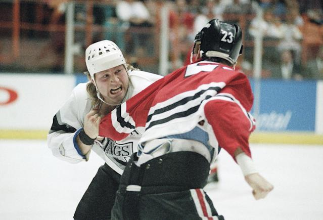 FILE - In this Jan. 30, 1993, file photo, Chicago Black Hawks Stu Grimson (23) gets set to unload a punch on Los Angeles Kings' Marty McSorley during NHL action in Inglewood, California. Fighting has been a part of the NHL for about as long as the sport has existed, though the fraternity of enforcers has dwindled through the years. (AP Photo/Chris Martinez, File)