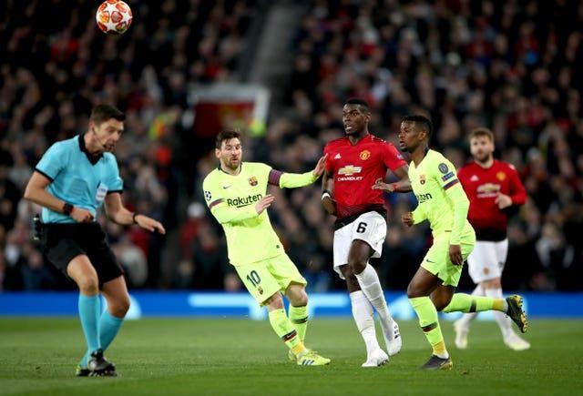 Manchester United's Paul Pogba, centre, battles for possession with Barcelona's Lionel Messi in the Champions League
