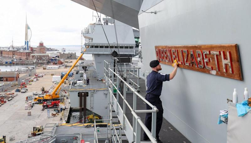 Able Seaman Ryan Whatmore, polishes the name board of HMS Queen Elizabeth (PA)