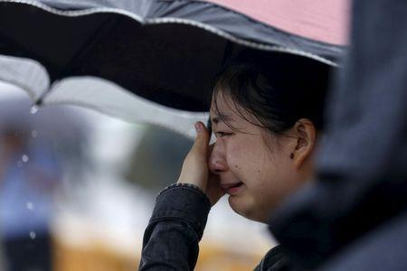 A relative of a missing passenger aboard a capsized ship cries on the banks of the Jianli section of Yangtze River in Hubei province, China, June 3, 2015. REUTERS/Aly Song
