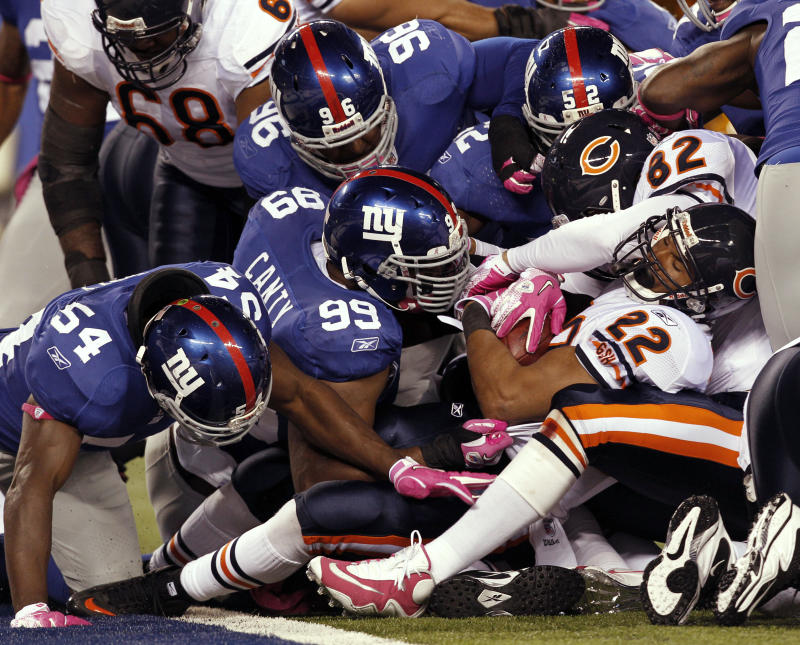 Chicago Bears running back Matt Forte (22) is tackled by New York Giants' Chris Canty (99) during the fourth quarter of an NFL football game at New Meadowlands Stadium, Sunday, Oct. 3, 2010, in East Rutherford, N.J. The Bears lost the game 17-3. (AP Photo/Kathy Willens)