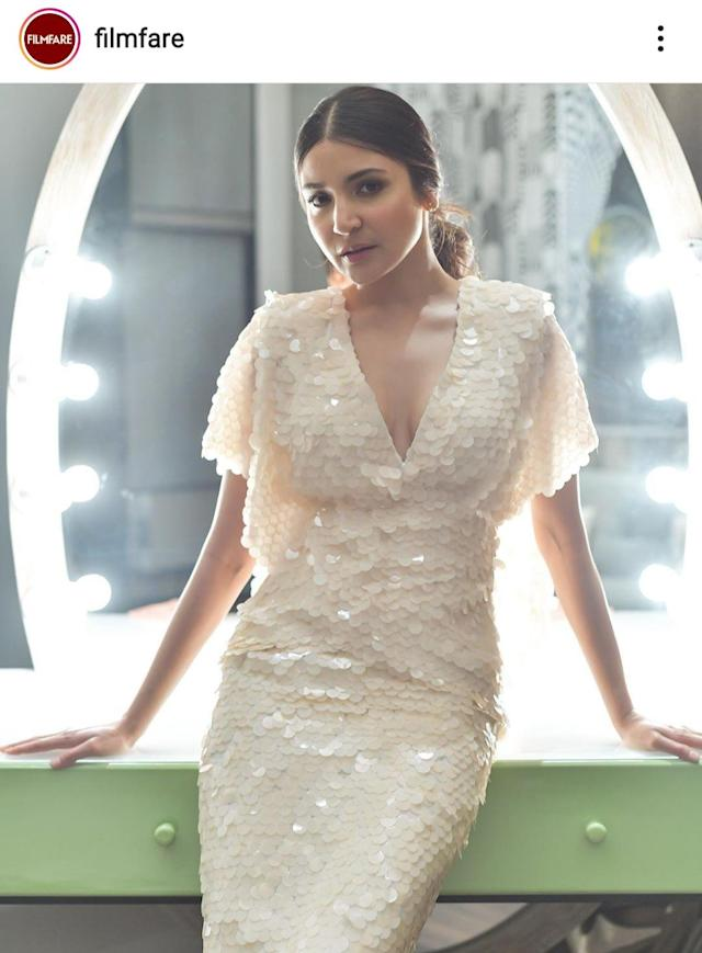 Anushka cuts an elegant figure in this white dress covered in sequins resembling fish scales. Channeling her inner mermaid, the actress styled herself in mid-partitioned hair settling in a neat pony at the back. Well-defined eyes and nude colors on the face kept the look appropriate for day time wear.