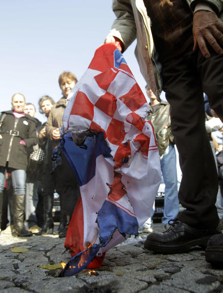 Protesters burn a Croatian flag during the protest in front of the presidency building in Belgrade, Serbia, Saturday, Nov. 17, 2012. A few hundred hardline Serbian nationalists have burned a Croatian flag angry that a U.N. war crimes court has overturned the convictions of two Croatian generals for murdering and expelling Serbs in a 1995 offensive. Serbia is furious that the appeals judges at the Hague court on Friday freed generals Ante Gotovina and Mladen Markac, who previously had been sentenced to lengthy prison terms for crimes against Serbs. (AP Photo/Darko Vojinovic)