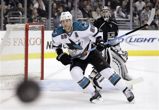 San Jose Sharks left wing Ryane Clowe and Los Angeles Kings goalie Jonathan Quick, background, look at the puck during the first period of an NHL hockey game in Los Angeles, Tuesday, March 20, 2012. (AP Photo/Jae C. Hong)