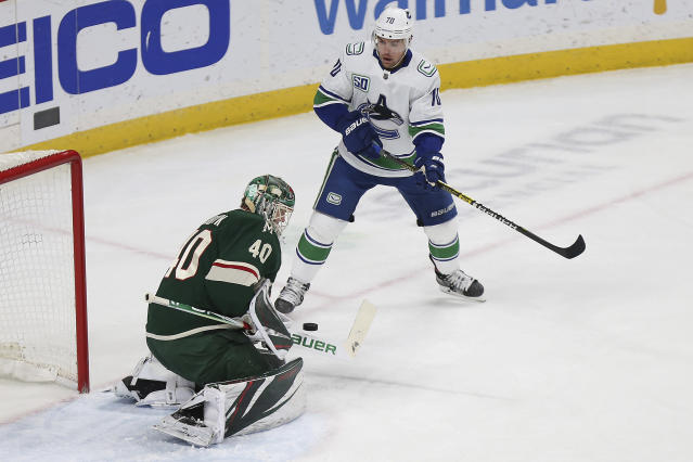 Minnesota Wild's goalie Devan Dubnyk (40) stops the puck in front of the net in the first period of an NHL hockey game against the Vancouver Canucks, Sunday, Jan. 12, 2020, in St. Paul, Minn. (AP Photo/Stacy Bengs)