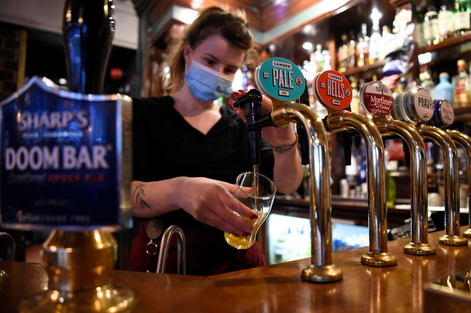 A server wearing a face mask or covering due to the COVID-19 pandemic, pours a pint of Camden Pale Ale inside a pub in Mayfair, London on November 3, 2020, as the country prepares for a second national lockdown during the novel coronavirus COVID-19 pandemic. - English pubs call last orders at the bar for a month on Wednesday evening, as the country effectively shuts down for the second time this year to try to cut coronavirus cases. (Photo by DANIEL LEAL-OLIVAS / AFP) (Photo by DANIEL LEAL-OLIVAS/AFP via Getty Images)