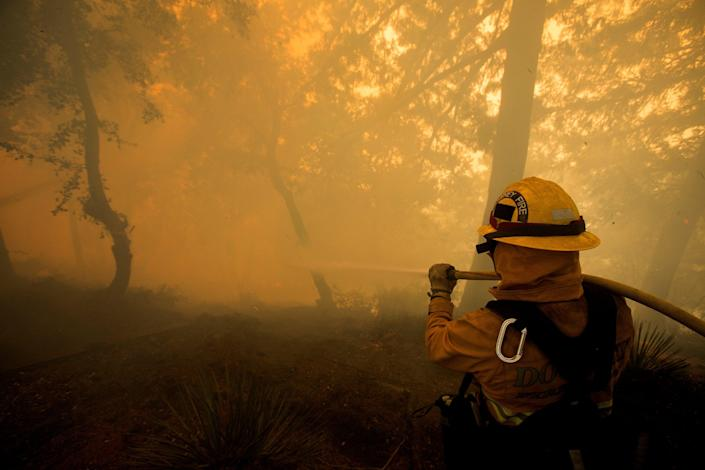 A firefighter battles a wildfire near a structure while defending the Mount Wilson observatory (REUTERS)