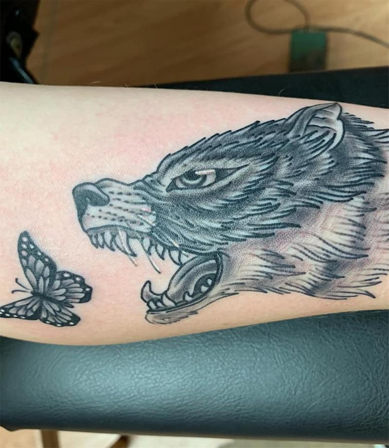 black and white tattoo of a wolf chasing a butterfly with its mouth open. it represents migraine, fibromyalgia and lupus