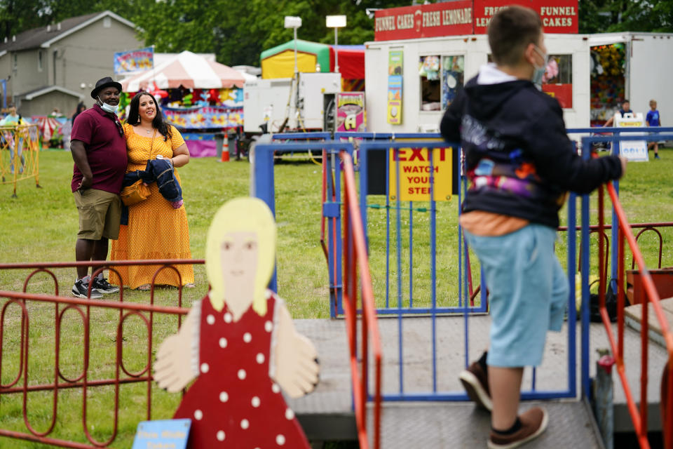 Alicia Duque, a 35-year-old mother of three and volunteer organizer for the progressive group, Action Together looks on with her husband Steve Edwards as their son Max waits to board a ride at the Edwardsville Pierogi Festival in Edwardsville, Pa., Friday, June 11, 2021. (AP Photo/Matt Rourke)