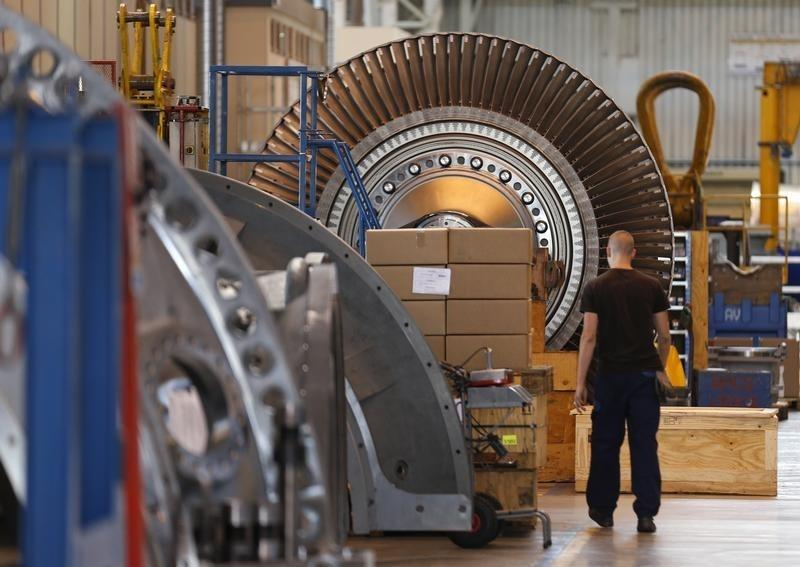 A worker walks past a gas turbine under construction at the gas turbines production unit of the General Electric plant in Belfort