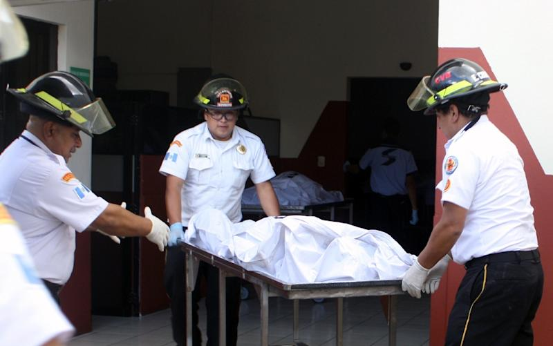 Guatemalan firefighters carry the corpse of one of the victims of a fatal blaze at a children's shelter in San Jose Pinula, on March 8, 2017 (AFP Photo/)