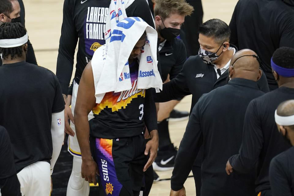 An injured Phoenix Suns guard Chris Paul (3) walks off the court during the first half of Game 1 of their NBA basketball first-round playoff series against the Los Angeles Lakers Sunday, May 23, 2021, in Phoenix. (AP Photo/Ross D. Franklin)