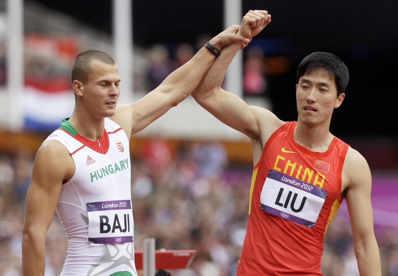 China's Liu Xiang, right, and Hungary's Balazs Baji, left, react after Liu's fall in a men's 110-meter hurdles heat during the athletics in the Olympic Stadium at the 2012 Summer Olympics, London, Tuesday, Aug. 7, 2012. (AP Photo/Anja Niedringhaus)