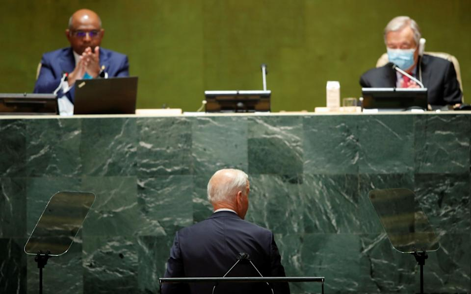 President Biden is applauded Tuesday by the president of the U.N. General Assembly, Abdulla Shahid of the Maldives, as U.N. Secretary-General Antonio Guterres looks on.