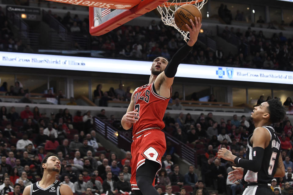 Chicago Bulls guard Zach LaVine (8) goes to the basket as San Antonio Spurs guard Dejounte Murray (5) and guard Bryn Forbes, left, defend him during the first half of an NBA basketball game Monday, Jan. 27, 2020, in Chicago. (AP Photo/David Banks)