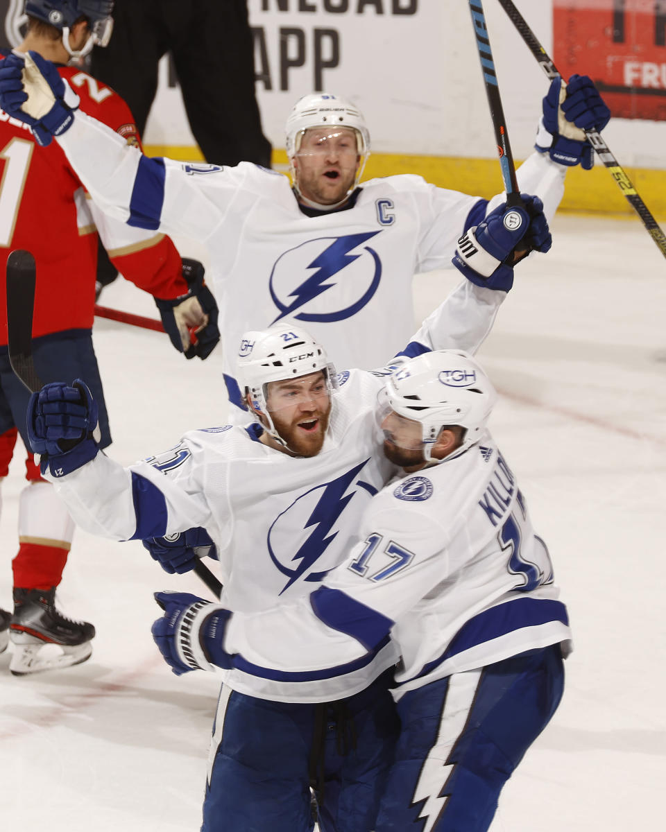 Tampa Bay Lightning center Steven Stamkos (91) and left wing Alex Killorn (17) celebrate the game-tying goal by defenseman Brayden Point (21) during the third period in Game 1 of an NHL hockey Stanley Cup first-round playoff series against the Florida Panthers, Sunday, May 16, 2021, in Sunrise, Fla. (AP Photo/Joel Auerbach)
