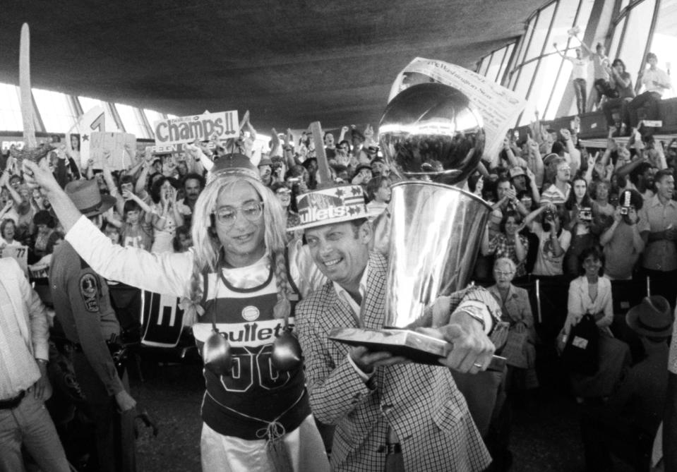 FILE - In this June 8, 1978 file photo, Washington Bullets owner Abe Pollin, holds up the NBA Championship trophy as the Bullets returned to Washington's Dulles Airport after defeating the Seattle SuperSonics . Among the huge crowd to greet the team was Barry Silberman, left, dressed as the operatic fat lady.  Pollin, the Washington Wizards owner who brought an NBA championship to the nation's capital and later had the mettle to stand up to Michael Jordan, died Tuesday, Nov. 24, 2009. He was 85. (AP Photo/Charles Tasnadi)