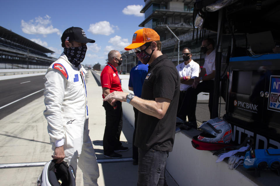 In this image provided by Jimmie Johnson Racing II, Inc., Seven-time NASCAR champion Jimmie Johnson, left, listens to a crew member during IndyCar during testing with Chip Ganassi Racing on the road course at Indianapolis Motor Speedway, Tuesday, July 28, 2020, in Indianapolis. Johnson is interested in competing in the IndyCar Series when he retires from full-time NASCAR competition at the end of this season. (Jimmie Johnson Racing II, Inc. via AP)