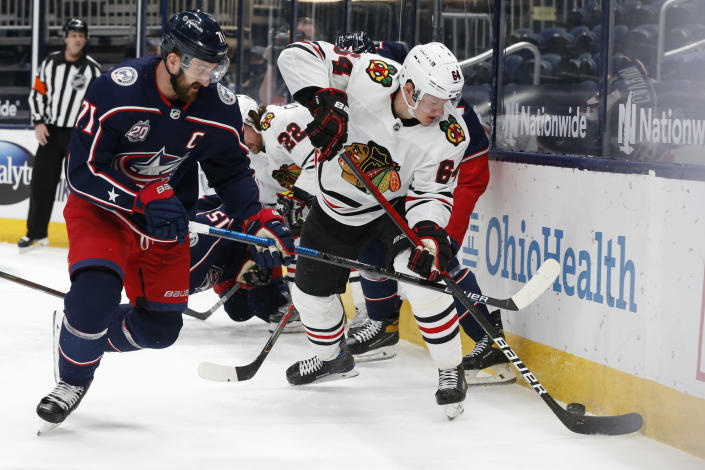 Chicago Blackhawks' David Kampf, right, tries to clear the puck as Columbus Blue Jackets' Nick Foligno defends during the first period of an NHL hockey game Thursday, Feb. 25, 2021, in Columbus, Ohio. (AP Photo/Jay LaPrete)