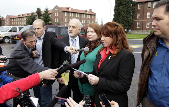 Kari Bales, third from right, stands next to attorney Lance Rosen, third from left, as she listens to her sister, Stephanie Tandberg, second from right, read a statement to reporters Tuesday, Nov. 13, 2012, outside the building housing a military courtroom on Joint Base Lewis McChord in Washington state, where a preliminary hearing ended Tuesday for Kari's husband, U.S. Army Staff Sgt. Robert Bales. Bales is accused of 16 counts of premeditated murder and six counts of attempted murder for a pre-dawn attack on two villages in Kandahar Province in Afghanistan in March of 2012. At right is Stephanie's husband, Eric Tandberg. (AP Photo/Ted S. Warren)