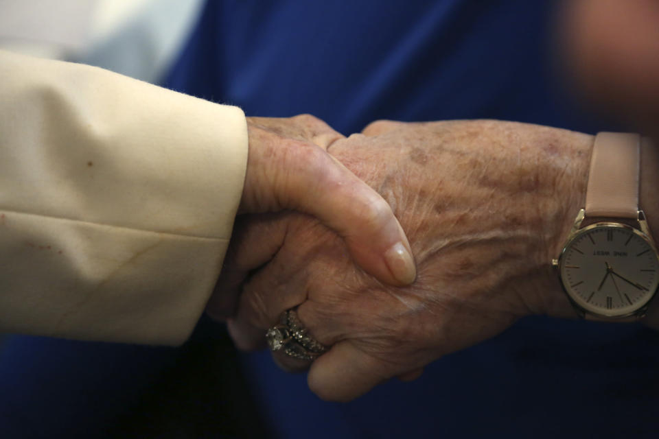 Holocaust survivors and friends Dolly Rabinowitz and Toby Goldberg hold hands as they talk about memories from World War II and their recent experiences with the coronavirus on Monday, June 14, 2021, at the Yeshivah of Flatbush theater at Joel Braverman High School in the Brooklyn borough of New York. The two women and dozens of other Holocaust survivors gathered for a concert honoring their lives and celebrating the end of their pandemic isolation. (AP Photo/Jessie Wardarski)