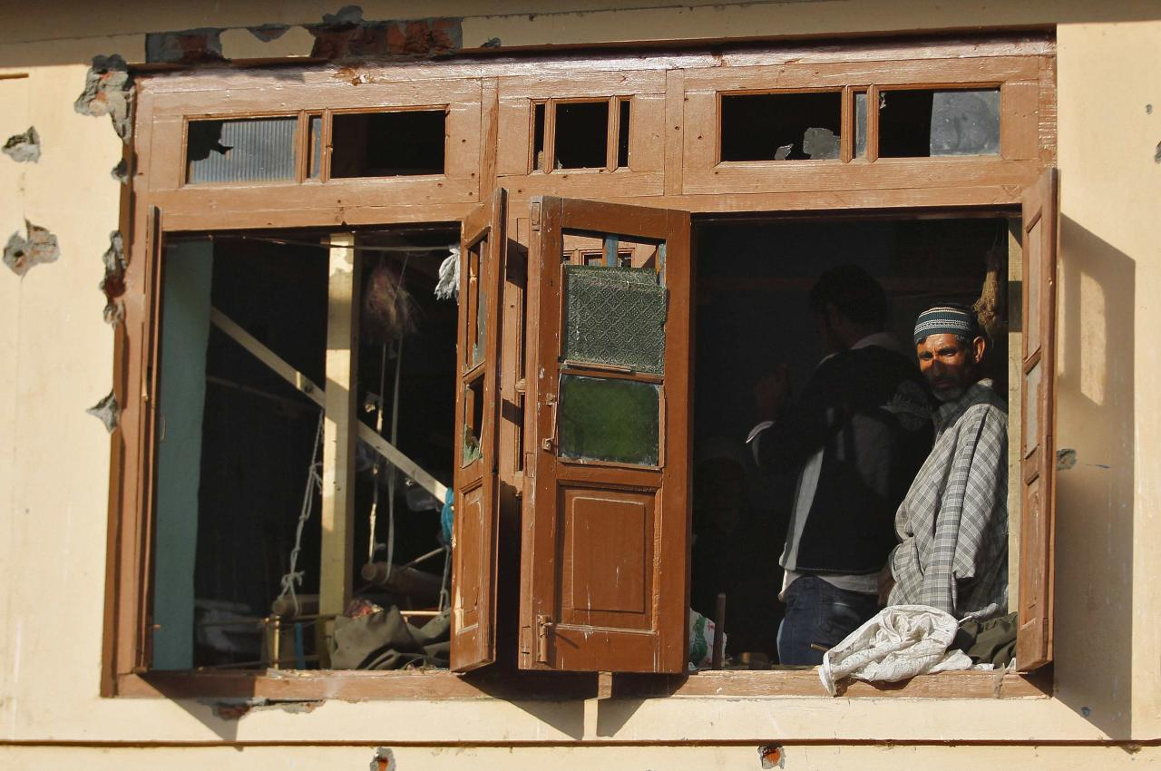A Kashmiri man watches through a damaged window of a residential house after a gun battle on the outskirts of Srinagar, October 3, 2013. At least five Indian policemen were injured in the overnight gunfight between militants and security forces, police said on Thursday. REUTERS/Danish Ismail (INDIAN-ADMINISTERED KASHMIR - Tags: CIVIL UNREST SOCIETY)