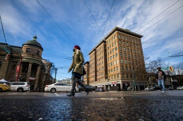 People cross East Hastings street near Main Street in Vancouver on Tuesday.