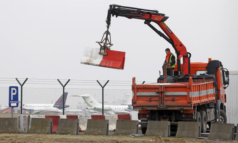 FILE - In this Feb. 19, 2013 file photo workers place concrete blocks to block access to a security fence next to the tarmac at Brussels international airport. Police carried out a series of raids on Wednesday, May 8, 2013, in Belgium and detained 31 people in three countries in connection with a spectacular $50 million diamond heist pulled off with apparent clockwork precision at Brussels Airport, a Belgian prosecutor said Wednesday. (AP Photo/Yves Logghe, file)