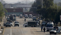 Security vehicles park near shipping containers placed by authorities on a highway to stop supporters of the 'Tehreek-e-Labaik Pakistan, a religious political party, entering into the capital during an anti-France rally in Islamabad, Pakistan, Monday, Nov. 16, 2020. The supporters are protesting the French President Emmanuel Macron over his recent statements and the republishing in France of caricatures of the Muslim Prophet Muhammad they deem blasphemous. (AP Photo/Anjum Naveed)