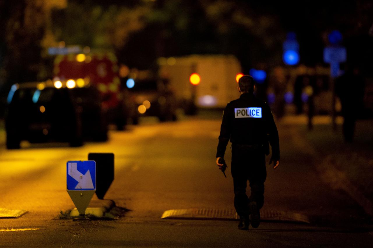 A French police officer stands guard a street in Eragny on October 16, 2020, where an attacker was shot dead by policemen after he decapitated a man earlier on the same day in Conflans-Sainte-Honorine. - French anti-terror prosecutors said Friday they were investigating an assault in which a man was decapitated on the outskirts of Paris and the attacker shot by police. The attack happened at around 5 pm (1500 GMT) near a school in Conflans Saint-Honorine, a western suburb of the French capital. The man who was decapitated was a history teacher who had recently shown caricatures of the Prophet Mohammed in class. French prosecutors are treating the attack as a terror incident, which coincides with the trial of alleged accomplices of the 2015 Charlie Hebdo attackers and comes weeks after a man injured two people he thought worked for the magazine. (Photo by Abdulmonam EASSA / AFP) (Photo by ABDULMONAM EASSA/AFP via Getty Images)