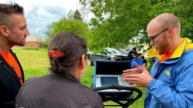 A worker with SNC Lavalin, right, shows community members the ground-penetrating radar equipment being used to search for graves at a cemetery site located behind where the Lac La Ronge Indian Residential School in La Ronge, Sask., once stood.  (Tammy Cook-Searson/Facebook - image credit)