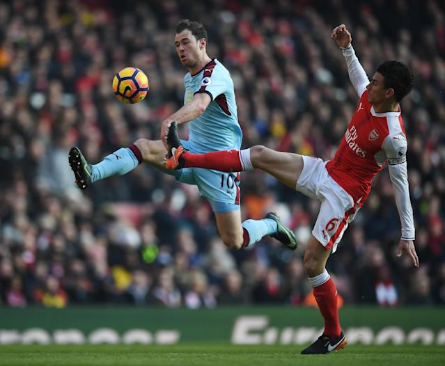 <p>Laurent Koscielny tries to stop Ashley Barnes </p>