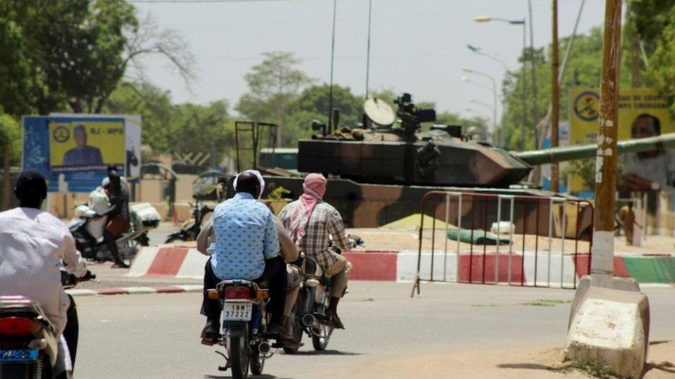People riding on motorbikes past a tank near the presidential palace in N'Djamena, Chad