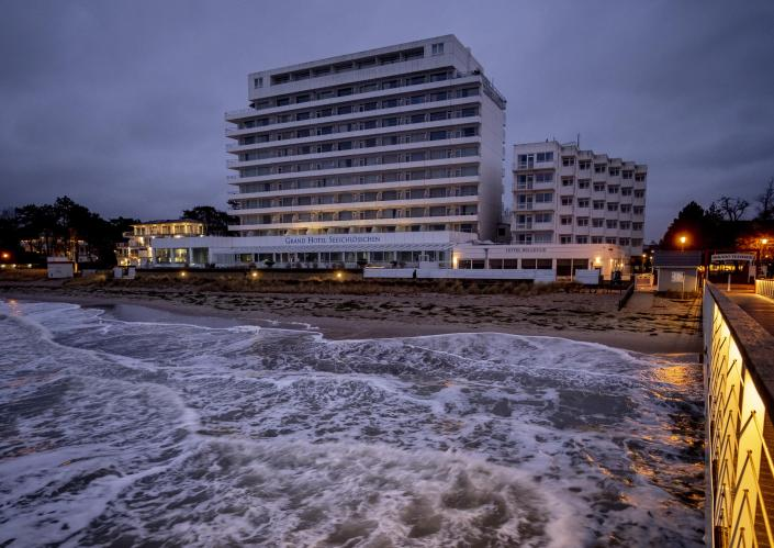 Waves land at the beach in Timmendorfer Strand at the Baltic Sea, Germany, Tuesday, Jan. 5, 2021. In background a five star hotel which is closed due to the Coronavirus. (AP Photo/Michael Probst)