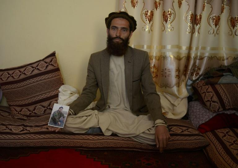 Afghan resident Ahmadullah poses for a photograph on April 24, 2017 with a picture of his brother Shir Mohammad, a soldier  killed in a Taliban attack on an army base on the outskirts of Mazar-i- Sharif