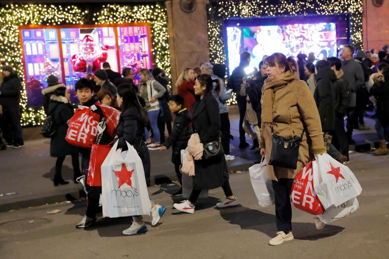 FILE PHOTO: People carry shopping bags from Macy's Herald Square during early opening for the Black Friday sales in Manhattan, New York City