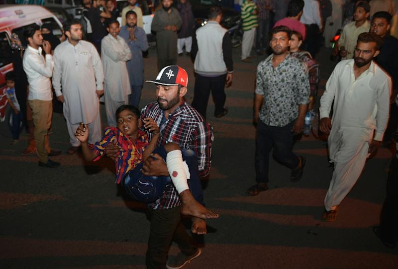 A Pakistani man carries an injured child to the hospital in Lahore on March 27, 2016, after a suicide bomb ripped through the parking lot of a crowded park in the Pakistani city of Lahore (AFP Photo/Arif Ali)