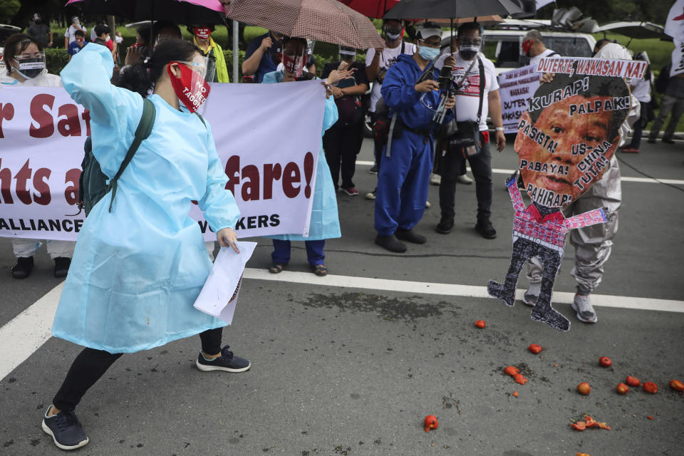 A protester hurls a tomato on a picture of Philippine President Rodrigo Duterte before marching towards the House of Representative where he is set to deliver his final State of the Nation Address in Quezon city, Philippines on Monday, July 26, 2021. Duterte is winding down his six-year term amid a raging pandemic and a battered economy. (AP Photo/Gerard Carreon)