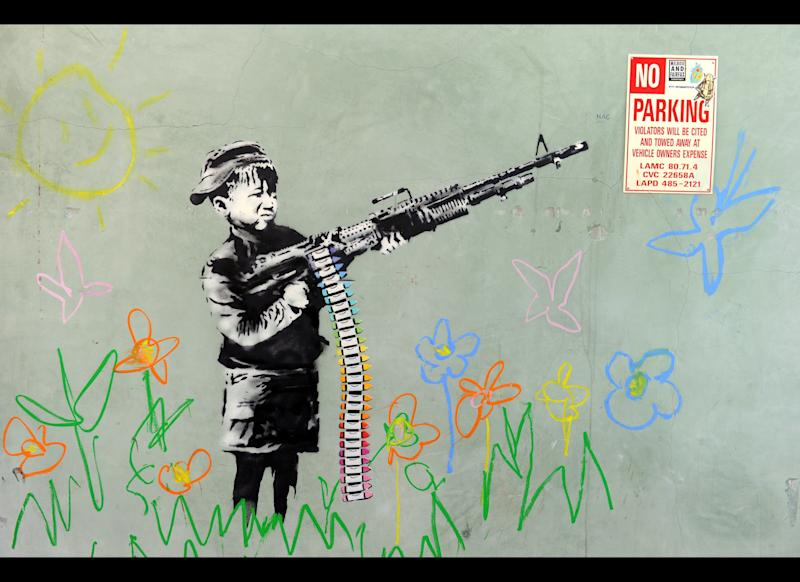 A graffiti attributed to secretive British artist Banksy depicting a child wielding a machine gun, in black and white surrounded by colored flowers, is spotted in Westwood, California on February 17, 2011. Another graffiti was ripped down Wednesday, February 16th in Hollywood, amid sightings of other pieces in a reported pre-Oscars publicity stunt. Banksy is nominated for best documentary for 'Exit Through the Gift Shop' at the Oscars, due to be announced on February 27th at the climax of Tinseltown's annual awards season. AFP PHOTO / GABRIEL BOUYS (Photo credit should read GABRIEL BOUYS/AFP/Getty Images)