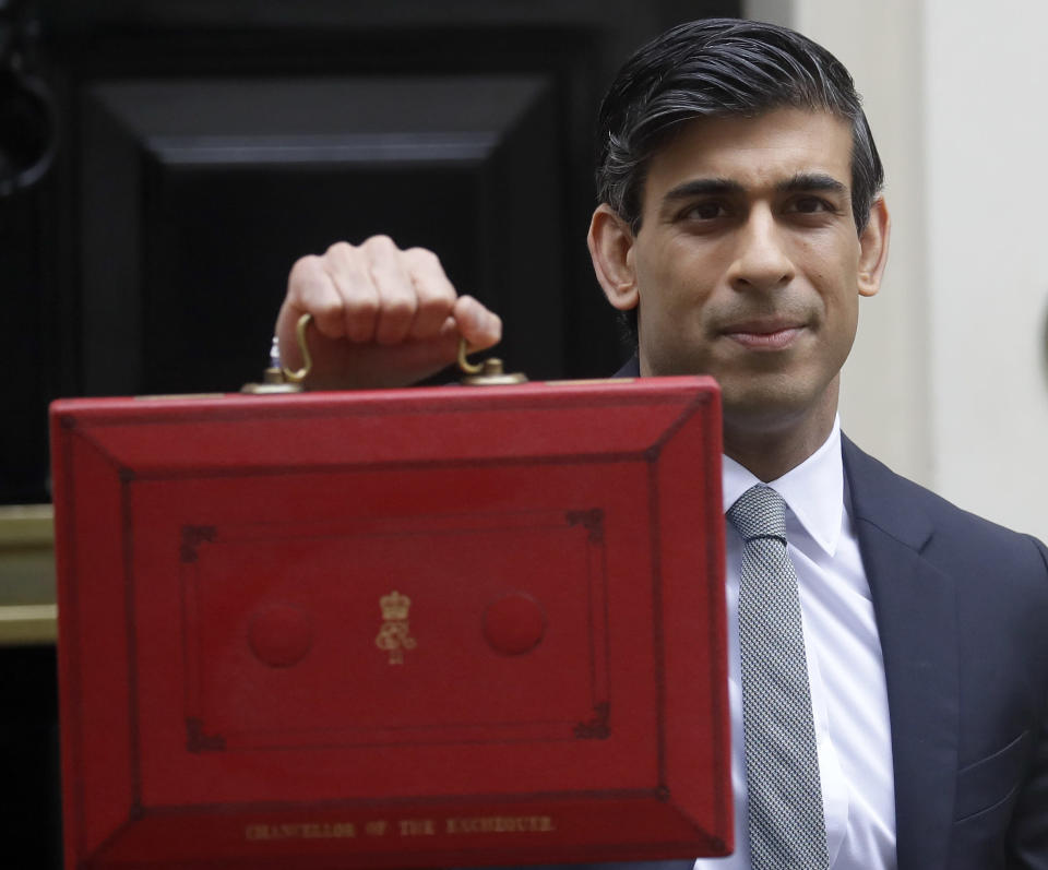 Britain's Chancellor Rishi Sunak stands with his red briefcase in front of 11 Downing Street in London, Wednesday, March 3, 2021. Sunak is expected to announce billions of pounds in tax cuts and spending increases to help workers and businesses hit by the coronavirus pandemic when he delivers his budget to Parliament on Wednesday. (AP Photo/Kirsty Wigglesworth)