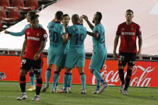 FC Barcelona's players celebrate Martin Braithwaite's goal during the Spanish La Liga soccer match between Mallorca and FC Barcelona at Son Moix Stadium in Palma de Mallorca, Spain, Saturday, June 13, 2020. With virtual crowds, daily matches and lots of testing for the coronavirus, soccer is coming back to Spain. The Spanish league resumes this week more than three months after it was suspended because of the COVID-19 pandemic. (AP Photo/Francisco Ubilla)